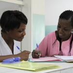 Two CURE Zambia nurses update a new patients admittance form