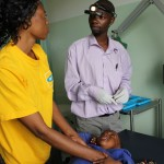 Patson Sakala (right) explains a procedure to a patient's mother in the ENT Clinic