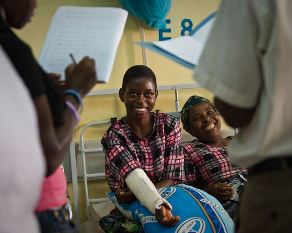 Idess and her mother listen cheerfully as doctors tell them she can begin extending her arm during physical therapy.