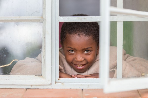 A little girl named Lydia peeks through a window in the outpatient clinic.