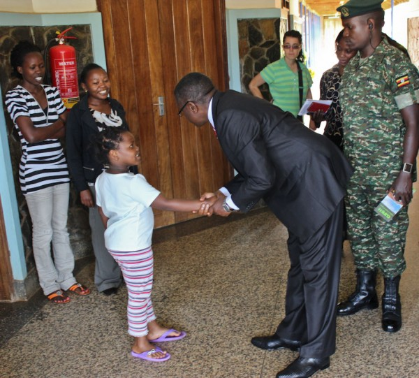 During a weekend visit to CURE, Charles Miyaga, prime minister of Buganda, stops to greet a staff member's child.